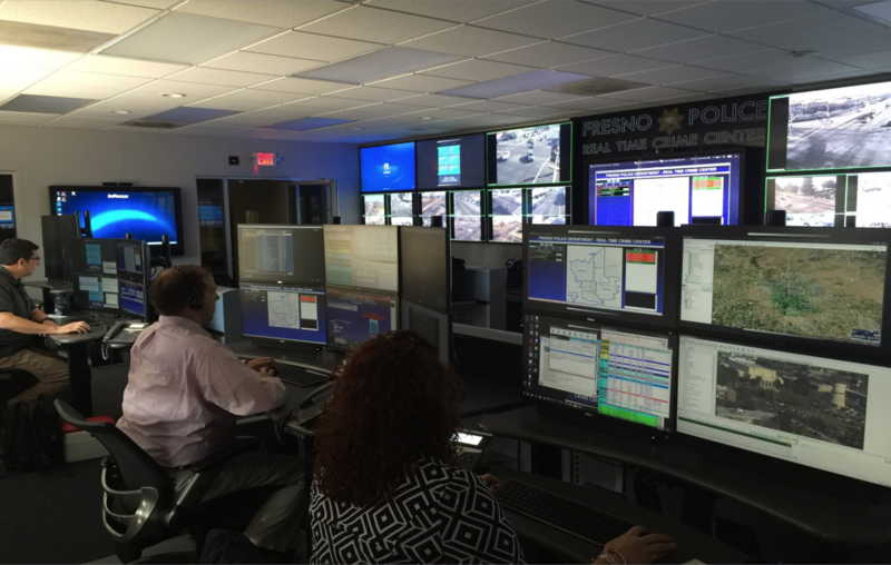 Police sit at workstations in front of a wall of video monitors.