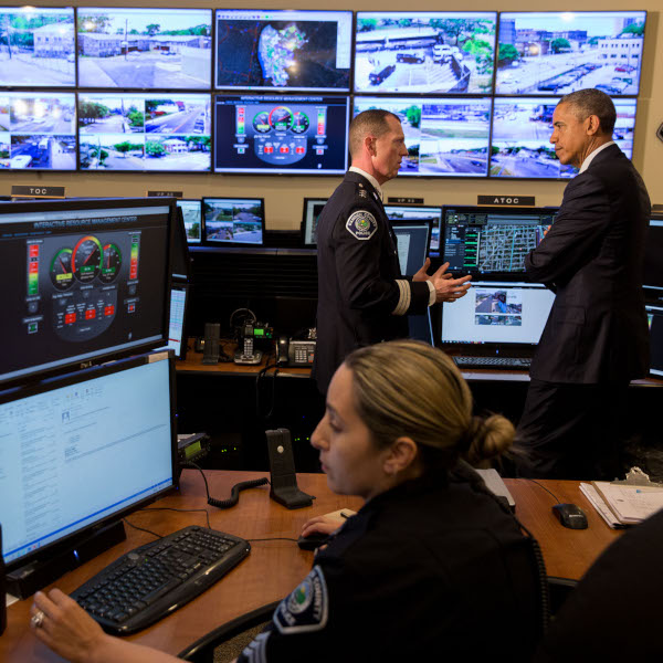 President Obama speaks to a police officer in a room full of computer monitors.