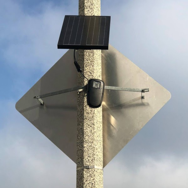 Flock brand automated license plate reader affixed to a light pole.